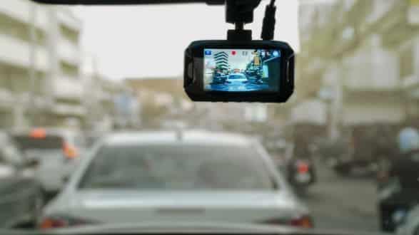 A dashboard camera attached to a windscreen